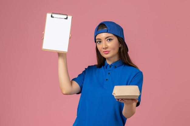 Corriere femminile di vista frontale in capo uniforme blu che tiene piccolo pacchetto di consegna vuoto con il blocco note sulla parete rosa, consegna dell'azienda di servizio dei dipendenti