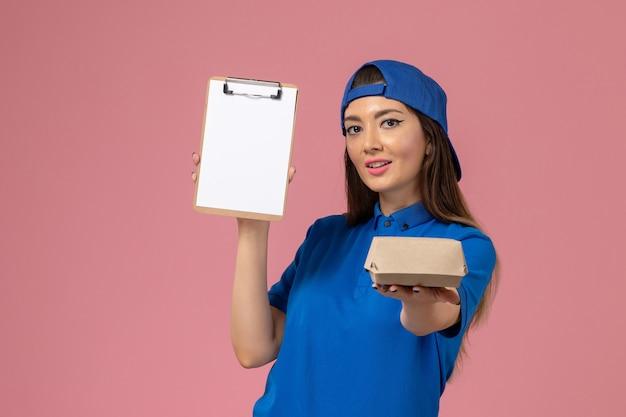 Corriere femminile di vista frontale in capo uniforme blu che tiene piccolo pacchetto di consegna vuoto con il blocco note sulla parete rosa, lavoratore di consegna dell'azienda di lavoro di servizio dei dipendenti