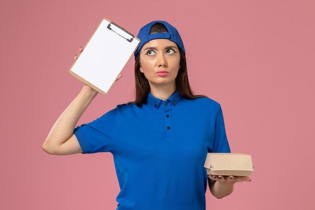 Corriere femminile di vista frontale in capo uniforme blu che tiene piccolo pacchetto di consegna vuoto con il blocco note sulla parete rosa, consegna dell'azienda di servizio del lavoro dei dipendenti