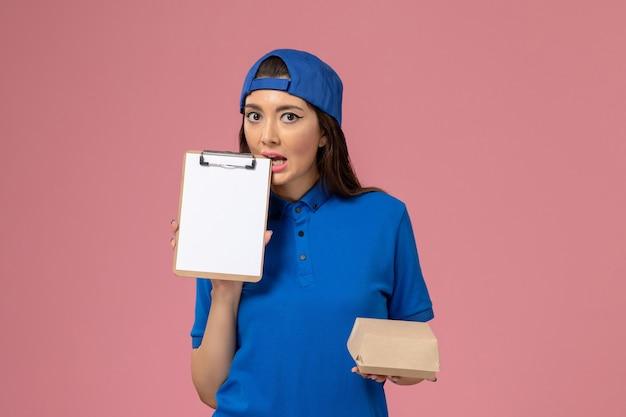 Corriere femminile di vista frontale in capo uniforme blu che tiene piccolo pacchetto di consegna vuoto con il blocco note sulla parete rosa, consegna dell'azienda di servizio dei dipendenti di lavoro