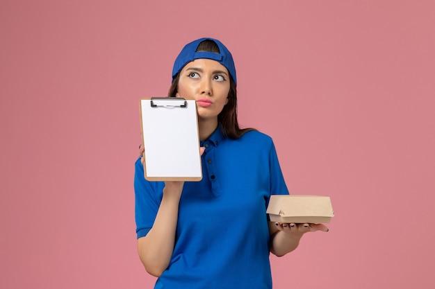 Corriere femminile di vista frontale in capo uniforme blu che tiene piccolo pacchetto di consegna vuoto con il blocco note che pensa sulla parete rosa, consegna dell'azienda di servizio dei dipendenti