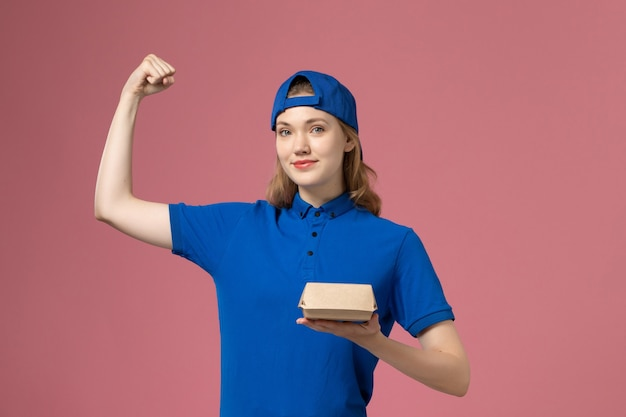 Corriere femminile di vista frontale in uniforme blu e mantello che tiene il piccolo pacchetto di cibo di consegna e che flette sulla parete rosa, società di servizi dell'uniforme di lavoro di consegna