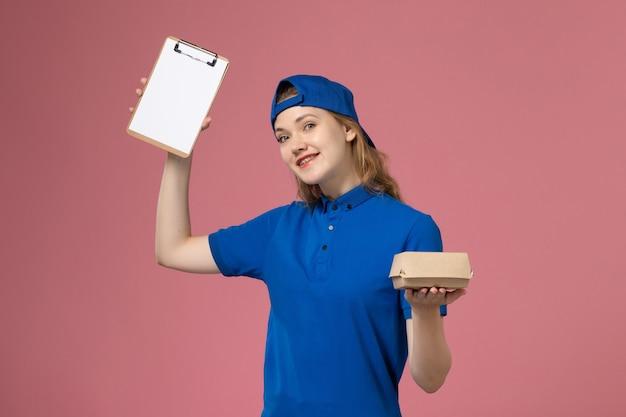 Corriere femminile di vista frontale in uniforme blu e mantello che tiene poco pacchetto di cibo di consegna e blocco note sulla parete rosa, lavoratore dipendente di servizio di consegna