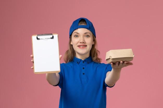 Corriere femminile di vista frontale in uniforme blu e mantello che tiene poco pacchetto di cibo di consegna e blocco note sulla parete rosa, impiegato del servizio di consegna