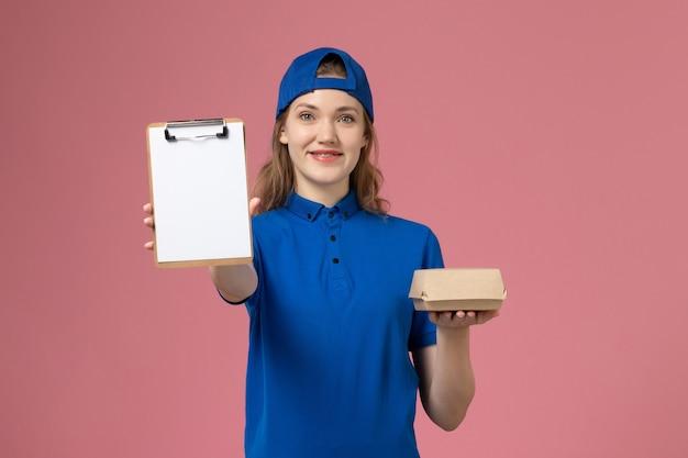 Corriere femminile di vista frontale in uniforme blu e mantello che tiene poco pacchetto di cibo di consegna e blocco note sulla parete rosa, impiegato di lavoro di servizio di consegna