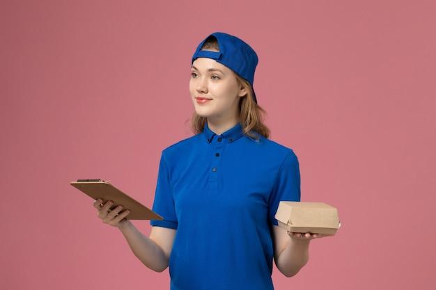 Corriere femminile di vista frontale in uniforme blu e mantello che tiene poco pacchetto di cibo di consegna e blocco note sulla parete rosa, impiegato di servizio del lavoro di consegna
