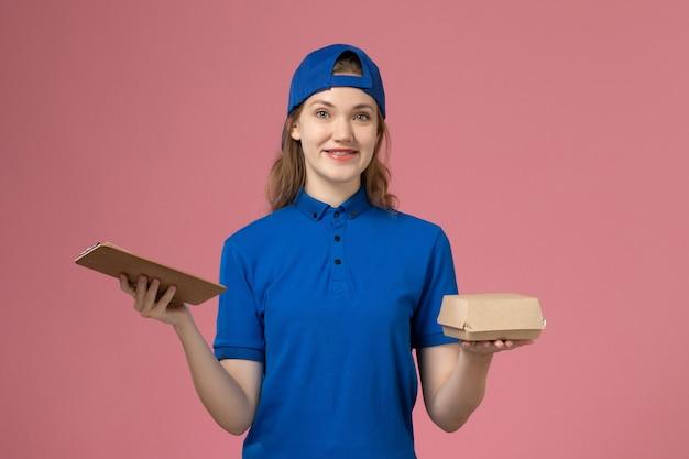 Corriere femminile di vista frontale in uniforme blu e mantello che tiene poco pacchetto di cibo di consegna e blocco note sulla parete rosa, dipendente del servizio di consegna della ragazza