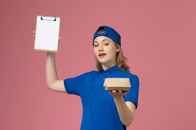 Front view female courier in blue uniform and cape holding little delivery food package and notepad on pink wall, worker delivery service employee