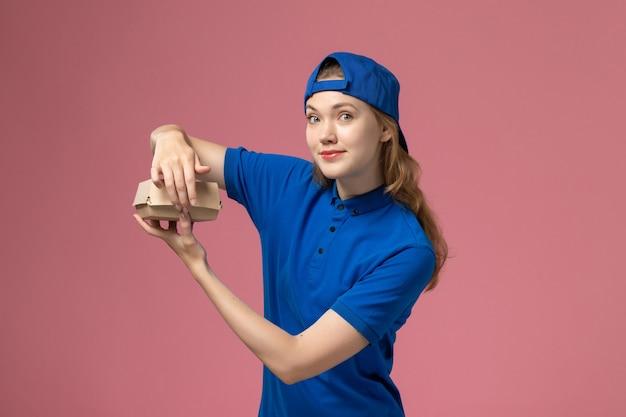 Corriere femminile di vista frontale in uniforme blu e mantello che tiene poco pacchetto di cibo di consegna sulla società di servizi uniforme di lavoro di consegna sfondo rosa