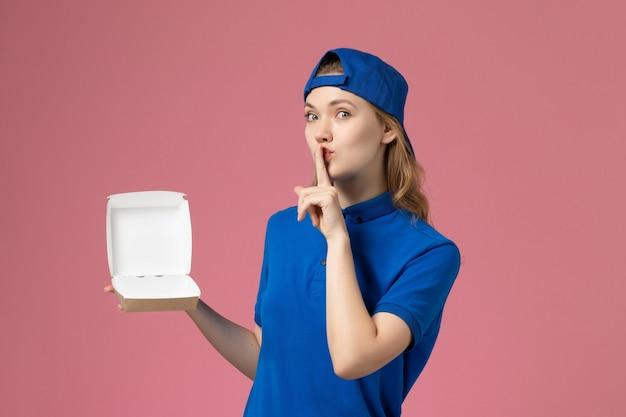 Corriere femminile di vista frontale in uniforme blu e mantello che tiene piccolo pacchetto di cibo di consegna sull'impiegato di lavoro di servizio uniforme di consegna sfondo rosa
