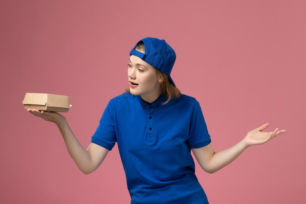 Front view female courier in blue uniform and cape holding little delivery food package on pink background job delivery uniform service company worker