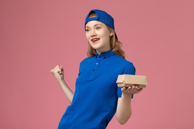 Corriere femminile di vista frontale in uniforme blu e mantello che tiene piccolo pacchetto di cibo di consegna su sfondo rosa lavoratore di società di servizio uniforme di consegna di lavoro