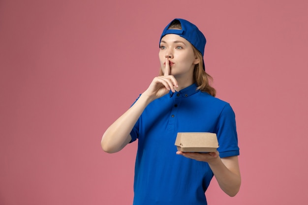 Front view female courier in blue uniform and cape holding little delivery food package showing silence sign on pink wall, delivery uniform service company