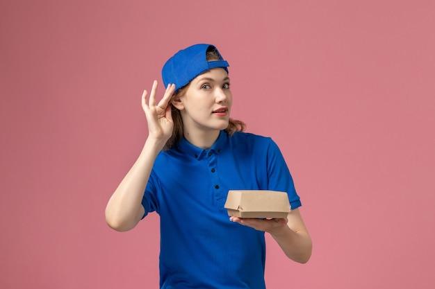 Corriere femminile di vista frontale in uniforme blu e mantello che tiene piccolo pacchetto di cibo di consegna cercando di sentire sul muro rosa, lavoro di società di servizi di consegna uniforme