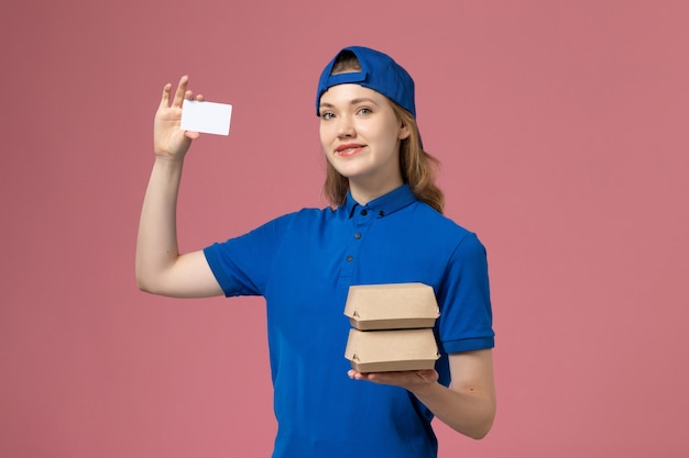 Front view female courier in blue uniform cape holding little delivery food packages and card on pink background service delivery employee