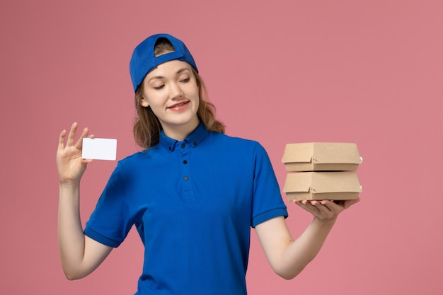 Front view female courier in blue uniform cape holding little delivery food packages and card on pink background service job delivery employee