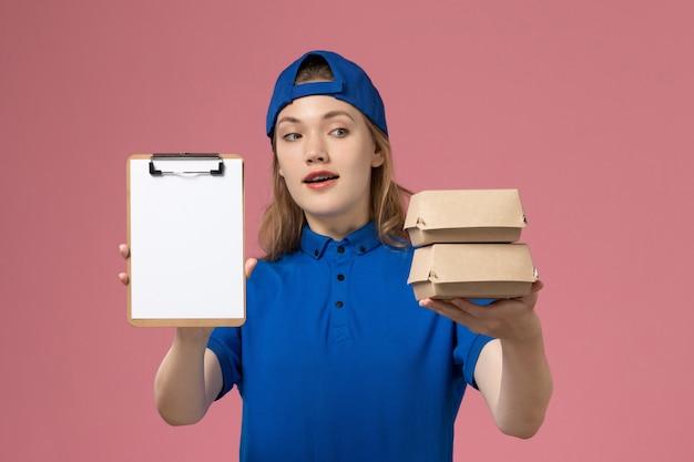Corriere femminile di vista frontale in capo uniforme blu che tiene piccoli pacchetti di cibo di consegna e blocco note sull'impiegato di servizio di lavoro di consegna sfondo rosa