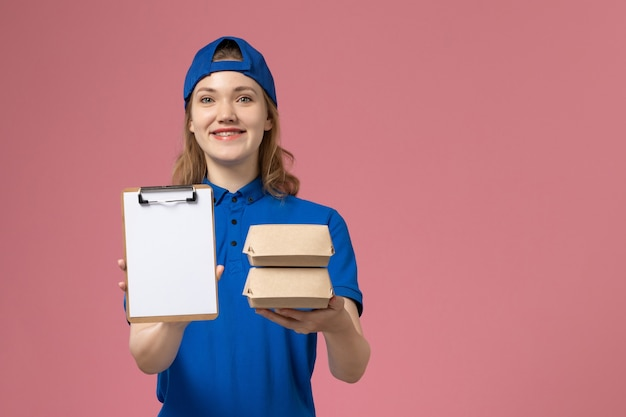 Corriere femminile di vista frontale in capo uniforme blu che tiene piccoli pacchetti dell'alimento di consegna e blocchetto per appunti sull'impiegato di consegna di servizio del fondo rosa