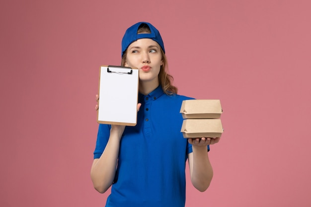 Front view female courier in blue uniform cape holding little delivery food packages and notepad thinking on pink background delivery service employee
