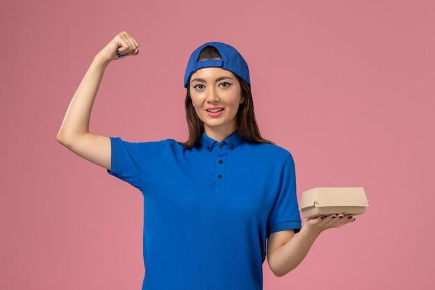 Corriere femminile di vista frontale in capo uniforme blu che tiene piccolo pacchetto di consegna e che flette sulla parete rosa, consegna del servizio dei dipendenti