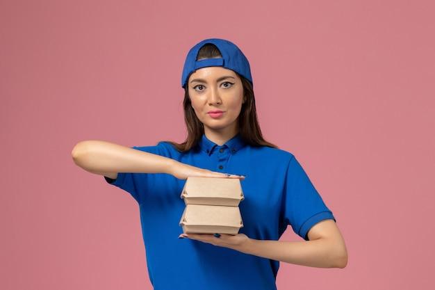 Corriere femminile di vista frontale in capo uniforme blu che tiene piccolo pacchetto di consegna sulla parete rosa, consegna del servizio di lavoro dei dipendenti