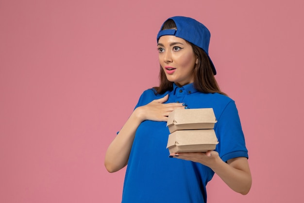 Corriere femminile di vista frontale in capo uniforme blu che tiene piccolo pacchetto di consegna sulla parete rosa, consegna del lavoro di servizio di lavoro dei dipendenti