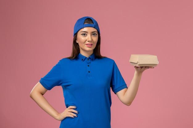 Corriere femminile di vista frontale in capo uniforme blu che tiene piccolo pacchetto di consegna sulla parete rosa, ragazza dell'operaio di lavoro di lavoro di consegna di servizio del dipendente