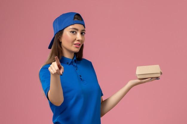 Corriere femminile di vista frontale in capo uniforme blu che tiene piccolo pacchetto di consegna sulla parete rosa, lavoro di lavoro di consegna di servizio di impiegato
