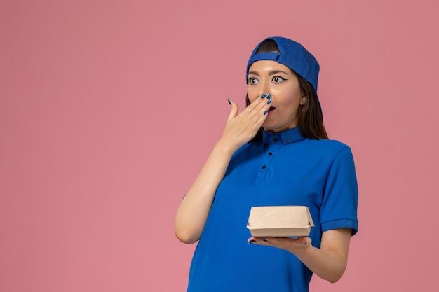 Corriere femminile di vista frontale in capo uniforme blu che tiene piccolo pacchetto di consegna sulla parete rosa, azienda della ragazza dell'operaio del lavoro di consegna di servizio del dipendente