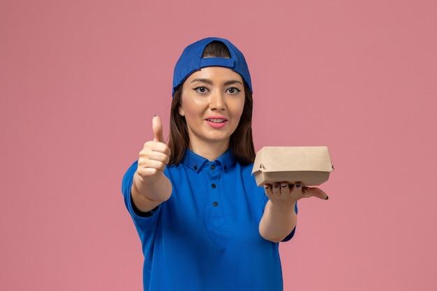 Corriere femminile di vista frontale in capo uniforme blu che tiene piccolo pacchetto di consegna sulla parete rosa, lavoro di servizio dei dipendenti