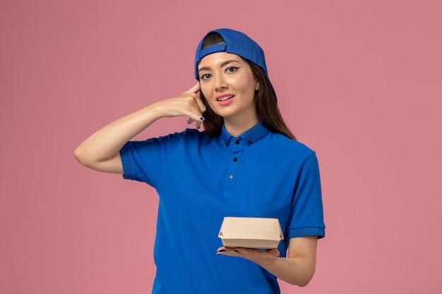 Corriere femminile di vista frontale in capo uniforme blu che tiene piccolo pacchetto di consegna sulla parete rosa, azienda di ragazza di lavoratore di lavoro di lavoro di servizio di dipendente