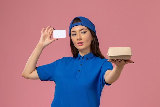 Corriere femminile di vista frontale in capo uniforme blu che tiene piccolo pacchetto di consegna con carta di plastica sulla parete rosa chiaro, consegna del servizio di lavoro dei dipendenti
