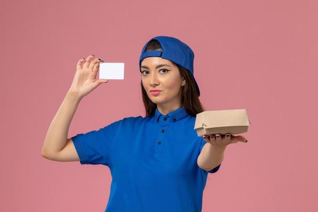 Corriere femminile di vista frontale in capo uniforme blu che tiene piccolo pacchetto di consegna con carta di plastica sulla parete rosa chiaro, lavoro di consegna di servizio dei dipendenti