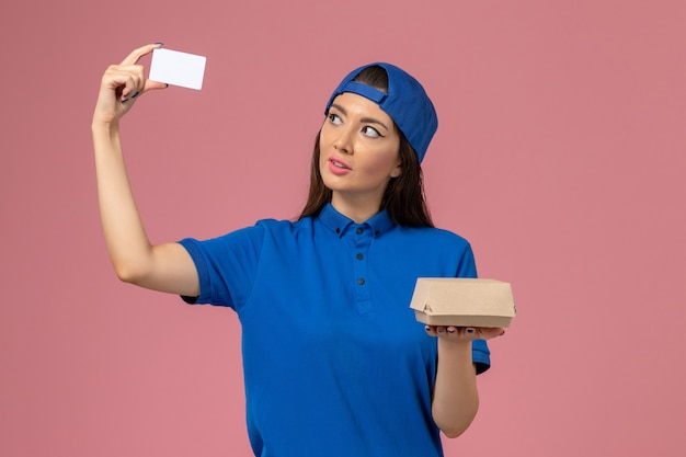 Front view female courier in blue uniform cape holding little delivery package with plastic card on light pink wall, employee service delivery work