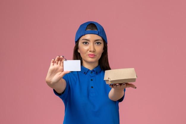 Corriere femminile di vista frontale in capo uniforme blu che tiene piccolo pacchetto di consegna con carta di plastica sulla parete rosa chiaro, lavoratore di consegna di servizio dipendente