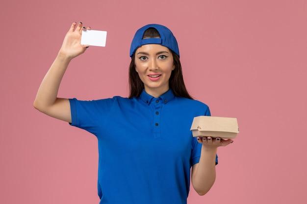 Corriere femminile di vista frontale in capo uniforme blu che tiene piccolo pacchetto di consegna con carta di plastica sulla parete rosa chiaro, consegna del servizio dei dipendenti