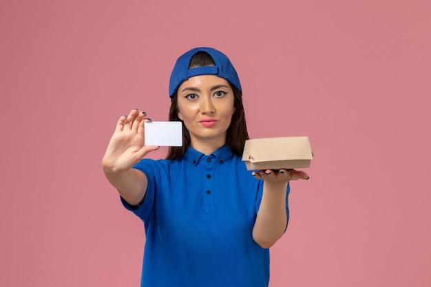 Corriere femminile di vista frontale in capo uniforme blu che tiene piccolo pacchetto di consegna con carta di plastica sulla parete rosa chiaro, consegna del servizio dipendente lavoro lavoro