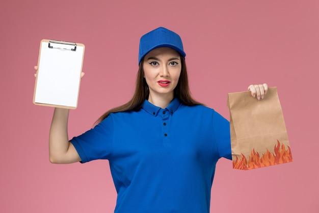 Corriere femminile di vista frontale in uniforme blu e mantello che tiene blocco note e pacchetto di cibo di carta sul muratore rosa