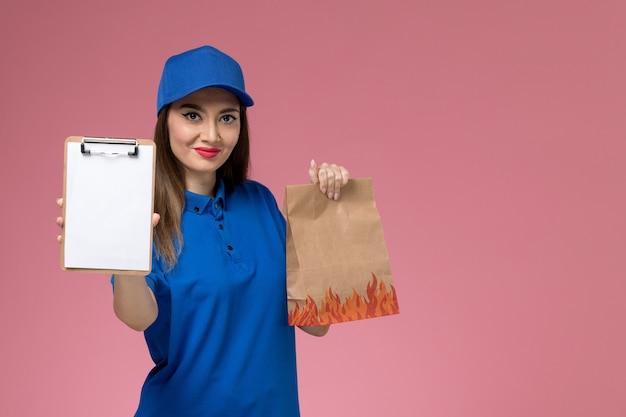 Corriere femminile di vista frontale in uniforme blu e mantello che tiene il blocco note con il pacchetto di cibo di carta sulla scrivania rosa