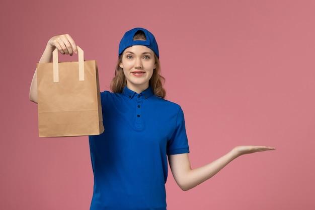 Corriere femminile di vista frontale in capo uniforme blu che tiene il pacchetto di consegna di carta sulla parete rosa, lavoro di lavoro degli impiegati di consegna di servizio