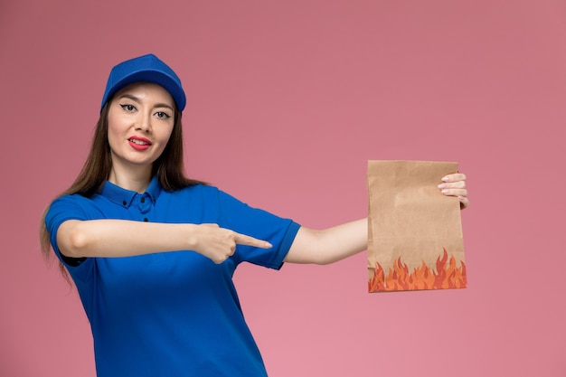 Corriere femminile di vista frontale in uniforme blu e mantello che tiene il pacchetto di cibo di carta sul muratore rosa