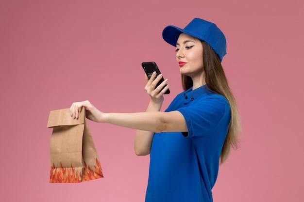 Corriere femminile di vista frontale in uniforme blu e capo che prende foto del pacchetto di cibo sulla parete rosa
