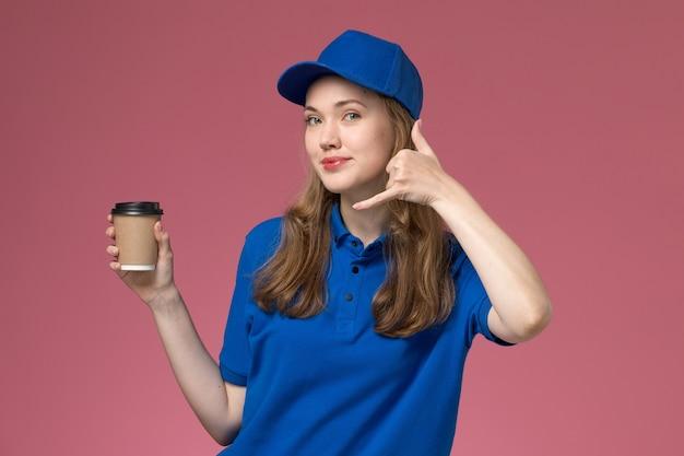 Corriere femminile di vista frontale in uniforme blu che tiene tazza di caffè marrone sull'uniforme di servizio scrivania rosa chiaro che consegna il lavoro dell'azienda