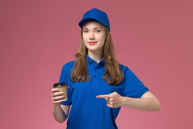 Corriere femminile di vista frontale in uniforme blu che tiene tazza di caffè marrone su fondo rosa uniforme di servizio che consegna il lavoro dell'azienda