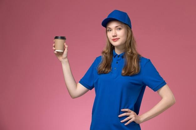 Corriere femminile di vista frontale in uniforme blu che tiene la tazza di caffè marrone sull'uniforme rosa di servizio della scrivania che consegna il lavoro di lavoro dell'azienda