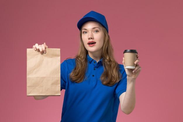 Corriere femminile di vista frontale in uniforme blu che tiene tazza di caffè marrone con il pacchetto di cibo su sfondo rosa chiaro uniforme di lavoro di servizio che consegna azienda