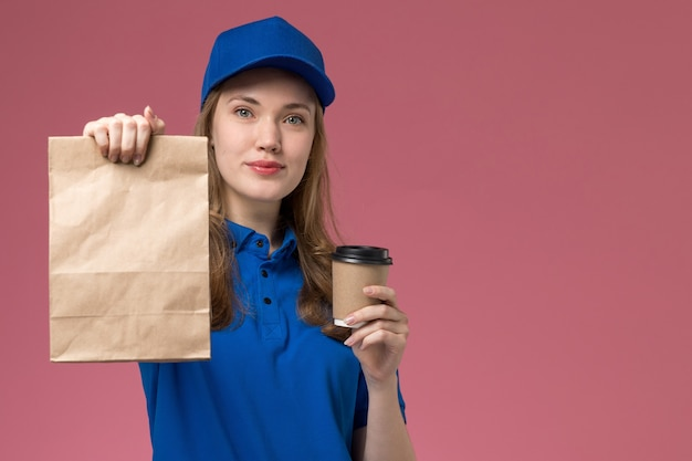 Corriere femminile di vista frontale in uniforme blu che tiene tazza di caffè marrone con il pacchetto di cibo e sorriso sulla società di consegna uniforme di servizio scrivania rosa chiaro