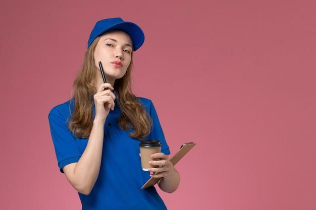 Corriere femminile di vista frontale in uniforme blu che tiene la tazza di caffè marrone con il blocco note e l'espressione di pensiero sull'uniforme di servizio di scrivania rosa chiaro che consegna l'azienda