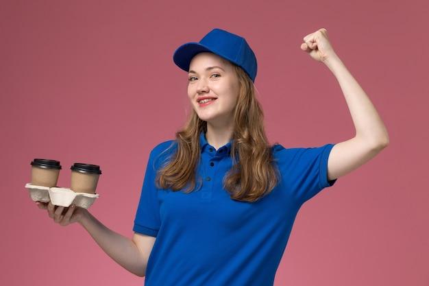 Corriere femminile di vista frontale in uniforme blu che tiene le tazze di caffè marroni che flettono con il sorriso sull'uniforme di servizio del fondo rosa che consegna il lavoro dell'azienda