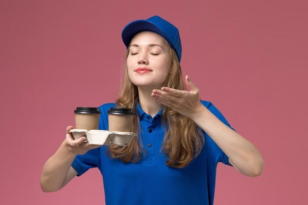 Corriere femminile di vista frontale in uniforme blu che tiene le tazze di caffè marroni che li odorano sull'uniforme di servizio del fondo rosa che consegna il lavoro dell'azienda
